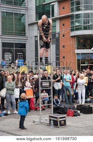 Manchester United Kingdom - September 24 2016: Street art performer on the stais performing his show with people enjoying the performance.