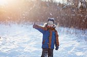 Happy little child playing throws up snow outdoors during snowfall. Active outoors leisure with children in winter on cold snowy days. poster