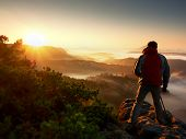 Happy photo enthusiast enjoy photography of fall daybreak in nature on cliff on rock. Dreamy fogy landscape misty sunrise in a beautiful valley below poster
