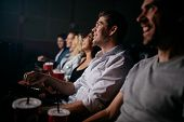 Group of young people sitting in cinema hall watching movie. Multiracial group of friends watching movie in theater. poster