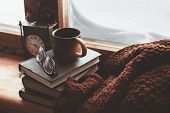 Warm and comfy winter concept. Book, cup of tea and sweater on wooden window sill in old house. Reading and relaxing in cold snowy weather at home. Quiet silent homely scene. poster