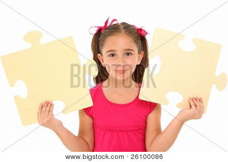 Beautiful 7 year old girl holding two large puzzle pieces over white background.