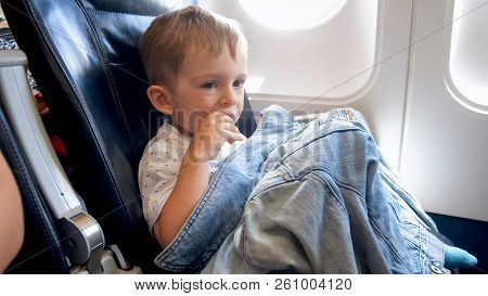 Little Toddler Boy Sitting In Airplane Seat And Having Snack