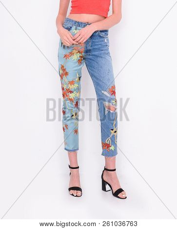 Fashion. Woman legs in embroidered flowers, jeans and high heels shoes posing