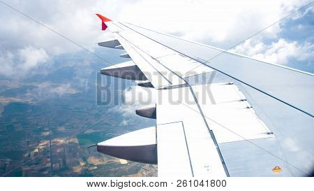 Image Of Airplane Wing Flying Above Land And Clouds