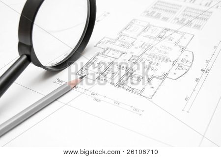 Architectural blueprint of house plan closeup with a pencil and magnifying glass. Closeup.