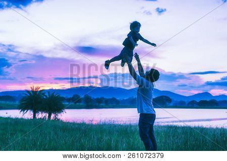 Silhouette The Happy Family; Father And Son Playing In The Park At The Sunset Sky;  People Having Fu