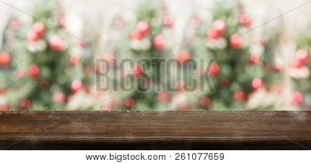 Empty Rustic Wood Table Top With Abstract Blur Christmas Tree Red Decor Ball And Snow Fall Backgroun