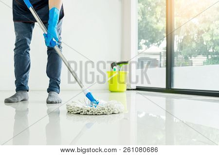 Young Housekeeper Cleaning Floor Mobbing Holding Mop And Plastic Bucket With Brushes, Gloves And Det