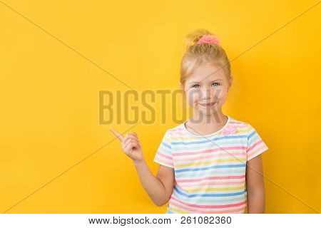 Portrait Of Stylish Little Girl With Finger Pointed Up. Little Child In Striped Shirt Has Idea. Kid