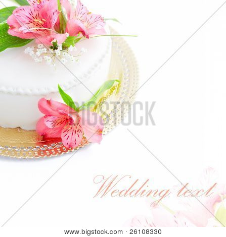 Half of wedding cake with fresh flowers on white background.