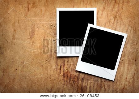 Two blank instant photo frames on old wooden background.