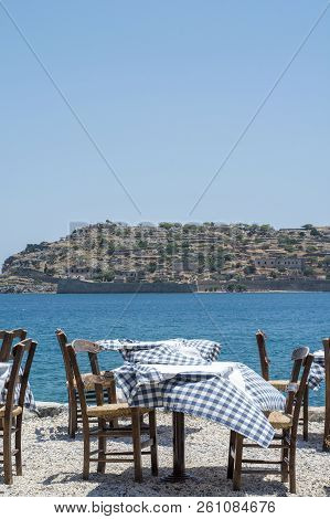 Several Wooden Tables And Chair Of The Street Restaurant In Greece In The Windy Day