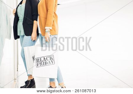 Black Friday. Cropped View Of A Couple Of Young Female Shoppers Holding Paper Shopping Bags While Ar