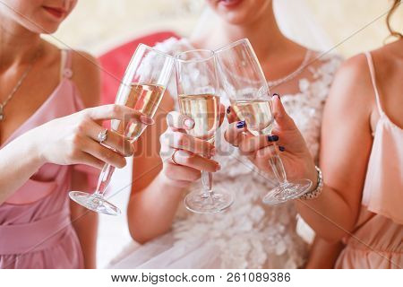Female Party With Glasses Of Champagne On The Bed. Witnesses And Fiancee Drink Champagne