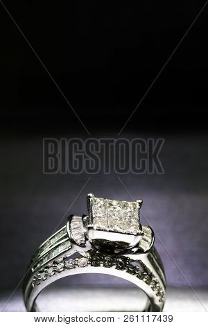 A Diamond Engagement Ring In A Box With Glint/reflection. Shimmering Princess-cut Diamonds.
