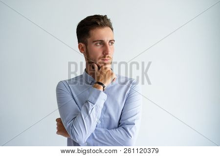 Frowning Business Leader Thinking Over Serious Decision. Confident Young Man In Formal Shirt Touchin