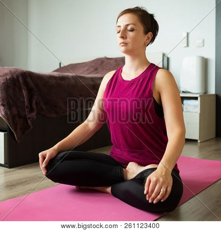 Attractive European Woman Exercising And Sitting In Yoga Position Practicing At Home.