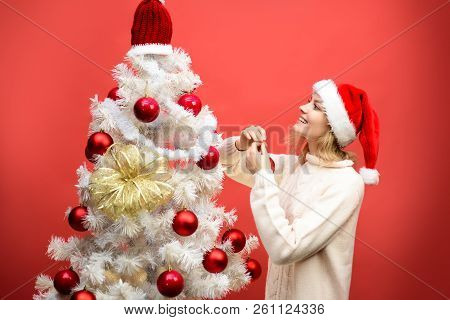 Preparing For Winter Holidays. Happy Girl In Santa Hat Decorating Christmas Tree. Christmas, New Yea