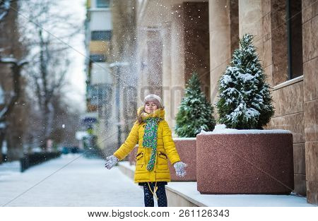 A little girl in a yellow jacket plays snowballs in the winter, throws snow, runs along a snowy road amid snowy fir trees and the city poster