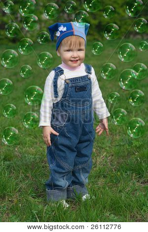 little baby and soap bubbles over green grass