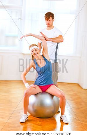 Smiling Girl Making Exercises On Fitness Ball Assisted By Her Personal Trainer