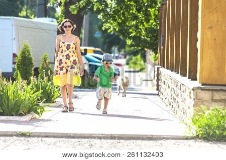 Mom And Child Are Walking Along The Street. A Woman And Her Son Are Walking Around The City. The Boy