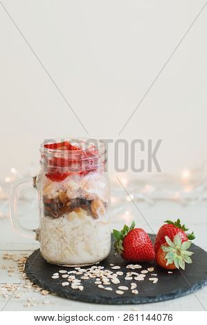 Homemade Overnight Oats With Fresh Strawberry Served In A  A Tall Glass Jar On Black Slate Board. He