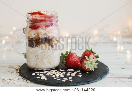 Overnight Oats With Strawberry Soaked In Coconut Milk In A Jar Served On Black Slate Board. Easy Bre