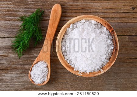 Crystals Of Large Sea Salt In A Wooden Bowl And Spoon And Dill On A Table.