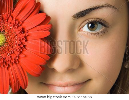 close-up woman eyes and red gerbera flower in front of her head
