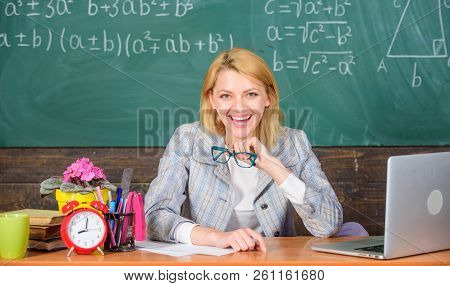 Online job boards or careers pages. Teacher cheerful pleasant woman educator sit table classroom work with laptop. Teacher happy work in school chalkboard background. Teacher job description poster