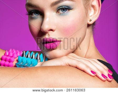 Closeup portrait of a beautiful fashion woman with bright makeup.  Gorgeous glamour girl of an attractive stylish girl. Portrait of a girl with bracelets  thorns. Jewelry.