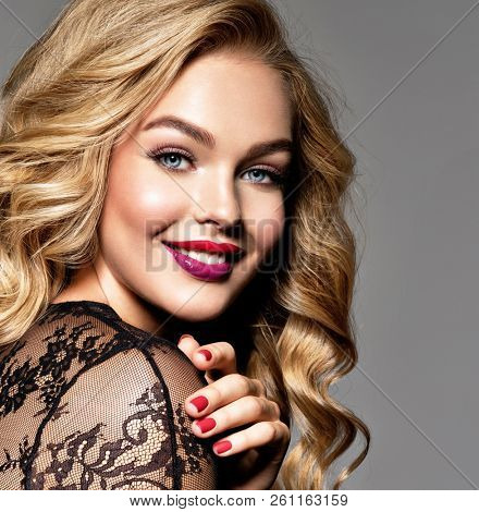 Blond smiling woman with long curly beautiful hair. Makeup. Fashion make-up. Fashionable girl dressed in black dress. Closeup portrait. Gorgeous face of an attractive fashion model. Bright red lips.