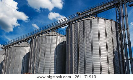 Steel Grain Silos Against Blue Sky With White Clouds. Steel Grain Silos Used To Store Grain.