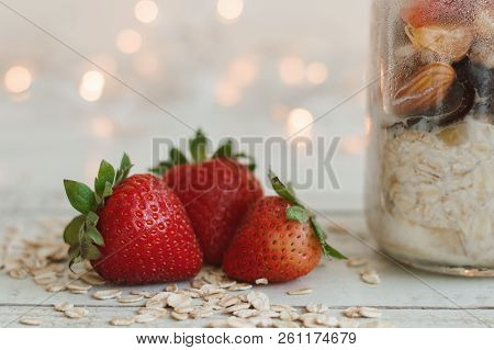 Fresh Strawberry, Whole Oats And Overnight Oats In A Bowl On Wooden Table, Blurred Bokeh Lights As B