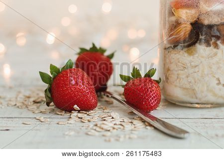 Fresh Strawberry, Whole Oats, Spoon And Overnight Oats In A Glass Bowl On Wooden Table