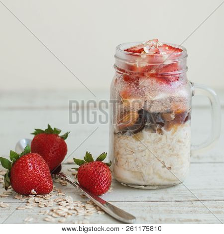 Square Photo Of Overnight Oats With Fresh Strawberry, Nuts And Dried Fruits Served On Wooden Table.