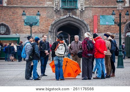 Bruges, Belgium - March, 2018: Group Of Tourists With A Free Walking Tour Guide At The Market Place