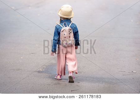 A Little Girl With A Backpack Going Along The Sidewalk. View From The Back.