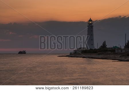 Lighthouse And Sunken Shipi In Sea At Sunset