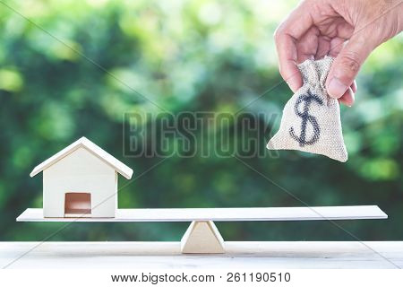 Balance Home And Money, Home Loan, Reverse Mortgage Concept : A Man Hand Put Us Dollar Money Bag Int