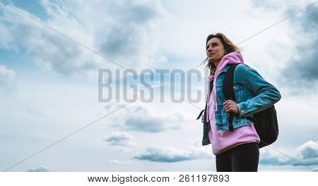 Tourist Traveler With Black Backpack On Background Mountain, Hiker Looks Up At Blue Sky Clouds, Girl