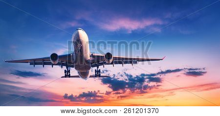 Landing Airplane Against Colorful Sky At Sunset. Landscape With Aircraft Is Flying In The Blue Sky W
