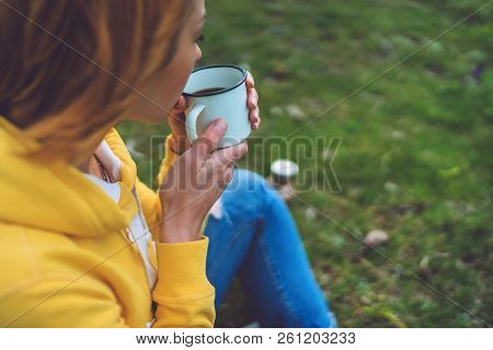 Happy Girl Holding In Hands Cup Of Hot Tea On Green Grass In Outdoors Nature Park, Beautiful Woman H