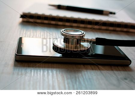 Stethoscope On A Black Smartphone Next To A Notepad And Biro - Fixing A Broken Mobile Phone Concept