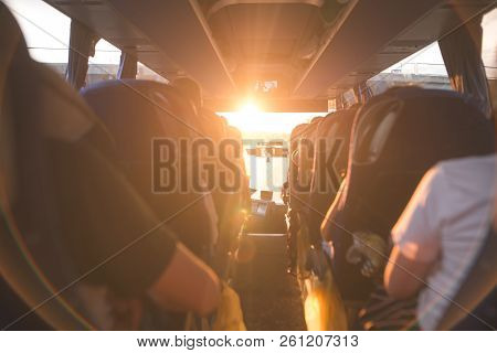 Background, Bus Interior. The Salon Of The Bus With People Fill The Sun With Light In The Sunset. Pe