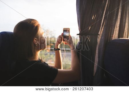 Tourist Woman Sits In A Bus Near The Window And Photographs Landscapes At Sunset On A Smartphone. To