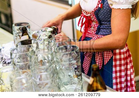 Beautiful Girl In A Dirndl Holding Mugs Filling Them With Beer Background Oktoberfest Glasses