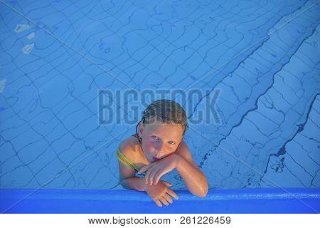 Cute Little Girl In The Public Swimming Pool. Portrait Of Little Cute Girl In The Swimming Pool. Sun